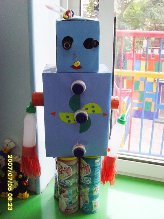 幼儿园 自制玩教具 :机器人  材料准备: 废纸盒、喜乐瓶、薯片捅、盒盖、彩胶纸、铁丝等 制作方法: 用薯片捅做成机器人的脚,用纸盒分别作机器人的身姿和头,用喜乐瓶做成机器人的胳膊。用铁丝将他们连在一起。用盒盖做成机器人的眼睛和扣子,再用彩胶纸进行装饰即可。 制作者: 邱燕春 闫 芳 北京市芳群第二幼儿园